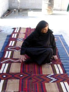 אמונה, יושבת על שטיח שארגה בעוג'א. אפשר לראות יפה את המרגום משתלב בשטיח
